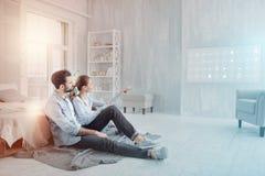 Λατρευτή συνεδρίαση ζευγών στο πάτωμα και τη TV προσοχής Στοκ Εικόνες