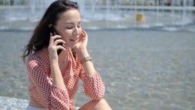 Λατρευτή, χαριτωμένη γυναίκα brunette, που κάθεται δίπλα στην πηγή πόλεων το καλοκαίρι απόθεμα βίντεο