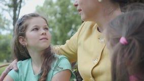 Λατρευτή ώριμη ευτυχής γιαγιά πορτρέτου που διδάσκει τις εγγονές της καθμένος στο όμορφο πάρκο κοντά σε μεγάλο απόθεμα βίντεο