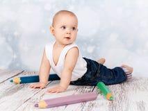 Λατρευτός λίγο μικρό παιδί που παίζει με τα μεγάλα κραγιόνια Στοκ εικόνα με δικαίωμα ελεύθερης χρήσης