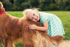 Λατρευτός λίγο ξανθό κορίτσι που αγκαλιάζει το σκυλί της στοκ εικόνα