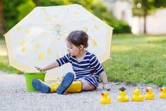 Λατρευτός λίγο παιδί στις κίτρινες μπότες βροχής και ομπρέλα στο summe Στοκ Φωτογραφίες