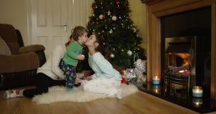 Λατρευτός γιος που τρώει ένα μήλο και που φιλά την όμορφη νέα μητέρα του κοντά στο χριστουγεννιάτικο δέντρο Ευτυχές χαμόγελο αδελ απόθεμα βίντεο