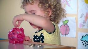 Λατρευτός λίγα χρήματα αποταμίευσης παιδιών σε μια piggy τράπεζα απόθεμα βίντεο