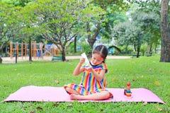 Λατρευτός λίγη ασιατική συνεδρίαση κοριτσιών παιδιών στο ρόδινο στρώμα και εφαρμογή του λοσιόν σωμάτων στο θερινό κήπο στοκ εικόνα