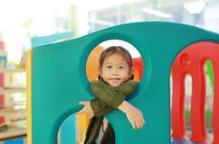 Λατρευτός λίγο ασιατικό θέατρο παιχνιδιών παιχνιδιού κοριτσιών παιδιών στην εσωτερική παιδική χαρά στοκ φωτογραφίες