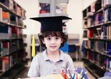 Λατρευτός λίγο παιδί, αγόρι, που κάθεται σε μια βιβλιοθήκη, που διαβάζει τα βιβλία στοκ φωτογραφία με δικαίωμα ελεύθερης χρήσης