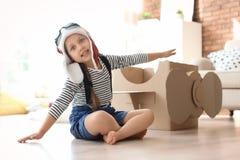 Λατρευτός λίγο παιδί που παίζει με το αεροπλάνο χαρτονιού στοκ εικόνες