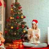 Λατρευτός ξανθός διαβάζει το παραμύθι στη Παραμονή Χριστουγέννων στο καπέλο santa Στοκ φωτογραφία με δικαίωμα ελεύθερης χρήσης