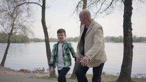 Λατρευτός παππούς πορτρέτου και χαριτωμένος λίγος εγγονός που περπατά στο πάρκο από κοινού Έννοια γενεών Φιλικός απόθεμα βίντεο