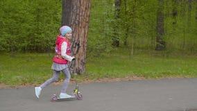 Λατρευτός το οδηγώντας μηχανικό δίκυκλο λακτίσματος κοριτσιών στο δρόμο στο πάρκο φιλμ μικρού μήκους