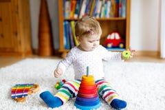 Λατρευτός χαριτωμένος όμορφος λίγο κοριτσάκι που παίζει με την εκπαιδευτική ζωηρόχρωμη ξύλινη rainboy πυραμίδα παιχνιδιών Στοκ φωτογραφίες με δικαίωμα ελεύθερης χρήσης