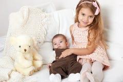 Λατρευτό λίγα κορίτσι και αγόρι παιδιών κάθονται στο κρεβάτι με τη teddy αρκούδα Στοκ Εικόνα
