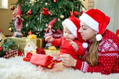 Λατρευτό λίγο άνοιγμα μωρών και μητέρων παρουσιάζει στα καπέλα santa γιορτάζει τα Χριστούγεννα Νέες διακοπές έτους ` s Στοκ Φωτογραφίες