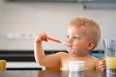 Λατρευτό αγοράκι ενός έτους βρεφών που τρώει το γιαούρτι με το κουτάλι Στοκ Εικόνες