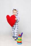 Λατρευτό αγοράκι στα πιτζάματα που κρατά μια μεγάλη κόκκινη καρδιά Στοκ Φωτογραφίες