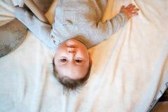 Λατρευτό αγοράκι στην άσπρη ηλιόλουστη κρεβατοκάμαρα Νεογέννητη χαλάρωση παιδιών στο κρεβάτι Βρεφικός σταθμός για τα μικρά παιδιά στοκ φωτογραφία με δικαίωμα ελεύθερης χρήσης
