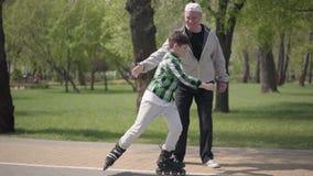Λατρευτό αγόρι ελεγμένο πουκάμισων στο πάρκο, ο παππούς του που πιάνει τον και που αγκαλιάζει Ενεργός ελεύθερος χρόνος απόθεμα βίντεο