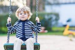 Λατρευτό αγόρι μικρών παιδιών που έχει την ταλάντευση αλυσίδων διασκέδασης στο υπαίθριο playgroun Στοκ φωτογραφία με δικαίωμα ελεύθερης χρήσης