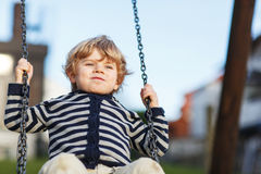 Λατρευτό αγόρι μικρών παιδιών που έχει την ταλάντευση αλυσίδων διασκέδασης στο υπαίθριο playgroun Στοκ εικόνα με δικαίωμα ελεύθερης χρήσης