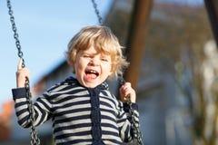 Λατρευτό αγόρι μικρών παιδιών που έχει την ταλάντευση αλυσίδων διασκέδασης στο υπαίθριο playgroun Στοκ εικόνες με δικαίωμα ελεύθερης χρήσης