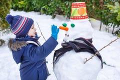 Λατρευτό αγόρι μικρών παιδιών που έχει τη διασκέδαση με το χιονάνθρωπο τη χειμερινή ημέρα Στοκ Εικόνες
