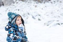 Λατρευτό αγόρι μικρών παιδιών που έχει τη διασκέδαση με το χιόνι τη χειμερινή ημέρα Στοκ φωτογραφία με δικαίωμα ελεύθερης χρήσης