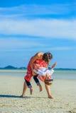 Λατρευτό αγόρι που έχει τη διασκέδαση με το mom του στην τροπική παραλία Άσπρη μπλούζα, σκοτεινά παντελόνι και γυαλιά ηλίου Χωρίς στοκ εικόνες