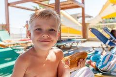 Λατρευτό αγόρι που τρώει το χοτ-ντογκ στην παραλία aquapark Στοκ φωτογραφίες με δικαίωμα ελεύθερης χρήσης