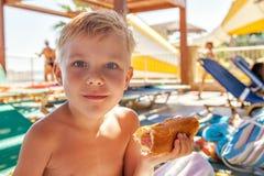 Λατρευτό αγόρι που τρώει το χοτ-ντογκ στην παραλία aquapark Στοκ εικόνες με δικαίωμα ελεύθερης χρήσης