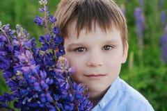 Λατρευτό αγόρι σε μια μπλε μπλούζα με μια ανθοδέσμη των λούπινων σε ένα λιβάδι στοκ εικόνα με δικαίωμα ελεύθερης χρήσης