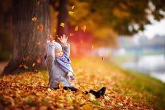Λατρευτό ευτυχές κοριτσάκι που πιάνει τα πεσμένα φύλλα, που παίζουν στο πάρκο φθινοπώρου Στοκ Εικόνα