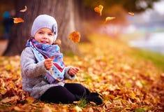 Λατρευτό ευτυχές κοριτσάκι που πιάνει τα πεσμένα φύλλα, που παίζουν στο πάρκο φθινοπώρου Στοκ εικόνα με δικαίωμα ελεύθερης χρήσης