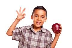 Λατρευτό ισπανικό αγόρι με τη Apple και το εντάξει σημάδι χεριών Στοκ εικόνα με δικαίωμα ελεύθερης χρήσης