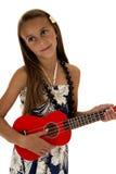 Λατρευτό κορίτσι μαυρίσματος που παίζει ένα κόκκινο ukulele σε ένα τροπικό φόρεμα στοκ εικόνες με δικαίωμα ελεύθερης χρήσης