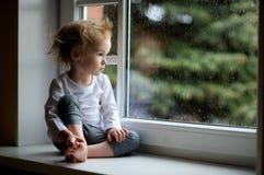 Λατρευτό κορίτσι μικρών παιδιών που κοιτάζει αν και το παράθυρο Στοκ εικόνες με δικαίωμα ελεύθερης χρήσης