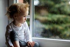 Λατρευτό κορίτσι μικρών παιδιών που κοιτάζει αν και το παράθυρο Στοκ Φωτογραφίες