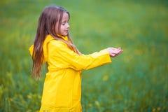 Λατρευτό κορίτσι μικρών παιδιών που φορά το αδιάβροχο παιχνίδι παλτών υπαίθρια μέχρι τη βροχερή και ηλιόλουστη ημέρα Στοκ Φωτογραφίες