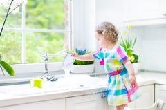 Λατρευτό κορίτσι μικρών παιδιών στα ζωηρόχρωμα πιάτα πλύσης φορεμάτων Στοκ Φωτογραφία