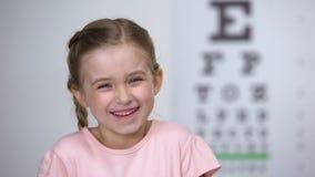Λατρευτό κορίτσι παιδιών που γελά μετά από τη δοκιμή οράματος στο διάγραμμα ματιών, υγιής θέα απόθεμα βίντεο