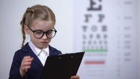 Λατρευτό κορίτσι παιδιών που προσποιείται να είναι γιατρός ματιών, μελλοντικό optometrist επαγγέλματος απόθεμα βίντεο