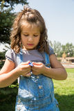 Λατρευτό κορίτσι παιδιών με το λουλούδι Θερινή πράσινη φύση Στοκ Εικόνες