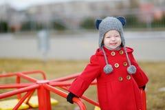 Λατρευτό κορίτσι που έχει τη διασκέδαση σε μια παιδική χαρά στην άνοιξη Στοκ εικόνες με δικαίωμα ελεύθερης χρήσης