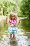 Λατρευτό κορίτσι στον ποταμό την ηλιόλουστη ημέρα στοκ εικόνα