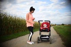 Λατρευτό κοριτσάκι έξω στον κόκκινο περιπατητή στους τομείς με τη μητέρα Νήπιο με το soother στοκ εικόνα με δικαίωμα ελεύθερης χρήσης