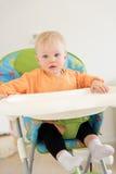 Λατρευτό κοριτσάκι με τα μπλε μάτια που κάθεται στο highchair Στοκ Φωτογραφία