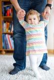Λατρευτό κοριτσάκι που κάνει τα πρώτα βήματα Περπάτημα κορών διδασκαλίας πατέρων κράτημα χεριών Στοκ Φωτογραφία