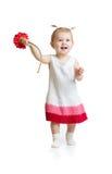 Λατρευτό κοριτσάκι που περπατά με το λουλούδι που απομονώνεται Στοκ Φωτογραφία