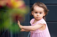 Λατρευτό κοριτσάκι στο ρόδινο θερινό φόρεμα στο σκοτεινό υπόβαθρο στοκ εικόνα με δικαίωμα ελεύθερης χρήσης