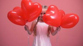 Λατρευτό κρύψιμο μικρών κοριτσιών πίσω από την καρδιά-διαμορφωμένη έκπληξη ημέρας βαλεντίνων μπαλονιών φιλμ μικρού μήκους